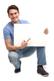 Young man pointing at blank board Royalty Free Stock Image