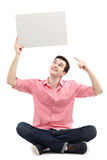 Young man pointing at blank sign. Young man holding blank poster Royalty Free Stock Image