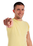 Young man pointing with finger. Attractive young man pointing with finger. All on white background. Selective focus on hand in foreground Stock Image