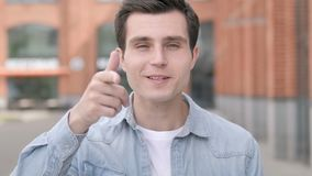 Young man pointing with finger outdoor stock video
