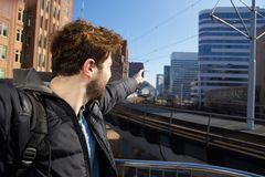 Young man pointing finger to buildings in the city Royalty Free Stock Photography