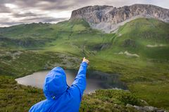 Young man pointing finger to the top of the rocky mountain Royalty Free Stock Images