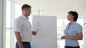 Young man pointing at flipchart gives presentation to his colleagues in office. Young man pointing at flipchart gives presentation to his colleagues in white and stock video footage