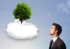 Young man pointing at a green tree on top of a white cloud Stock Photography