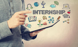 Young man pointing at Internship concept over a tablet Royalty Free Stock Photo