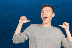 Young man pointing itself. Portrait of smiling young man pointing itself stock images