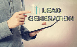 Young man pointing at Lead Generation text over tablet computer Royalty Free Stock Images