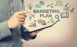 Young man pointing at Marketing Plan concept. Over a tablet computer stock images