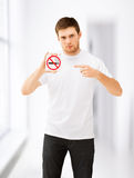 Young man pointing at no smoking sign stock image