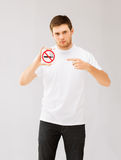 Young man pointing at no smoking sign stock photography