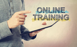 Young man pointing at Online Training text over tablet computer stock photography