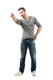 Young man pointing at something in the distance. Young man pointing at something or someone in the distance.  Full body length isolated over white background Stock Image