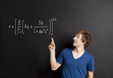 Young man pointing to a equation Royalty Free Stock Image