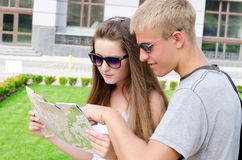 Young man pointing to a map. Young men pointing out a travel location on a map to his female travelling companion as they enjoy sightseeing on their summer Royalty Free Stock Images