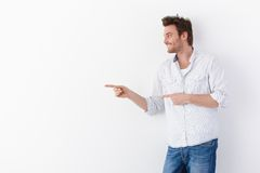 Young man pointing to right smiling Stock Photo