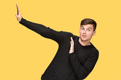 The young man pointing to something and looking at camera. On yellow studio background stock photos