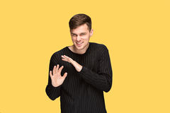 The young man pointing to something and looking at camera Stock Photo