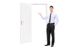 Young man pointing towards an opened door Royalty Free Stock Photo