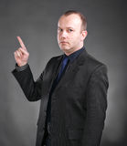 Young man pointing upwards. Portrait of seriousy young man pointing upwards on a gray background stock photo