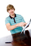 The young man points a finger at a blank sheet of sitting at the Royalty Free Stock Photos