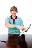 The young man points a finger at a blank sheet of sitting at the Stock Photos