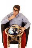 Young man pondering life with world globe in chair Royalty Free Stock Photo