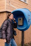 Young man with pony tale talking on street phone royalty free stock image