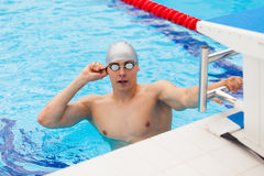 Young man in a pool - go to start swimming. backstroke during Stock Photos