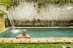 Young man in the pool. In a luxury villa royalty free stock photos