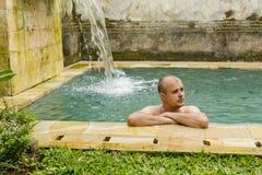 Young man in the pool. Young man in the pool in a luxury villa Stock Image