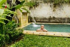 Young man in the pool. Young man in the pool in a luxury villa Stock Photography
