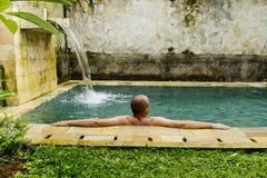 Young man in the pool. Young man in the pool in a luxury villa stock photo