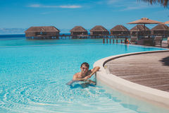 Young man in the pool and ocean in the background. Maldives Royalty Free Stock Images
