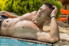 Young man by the pool. Young man posing by the pool Royalty Free Stock Images