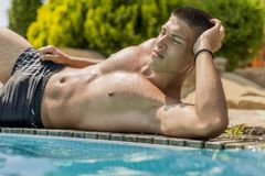 Young man by the pool. Young man relaxing by the pool on the sunny day Royalty Free Stock Image