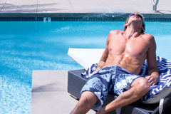Young Man By Pool Sunbathing Royalty Free Stock Photos