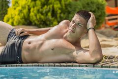 Young man by the pool. At sunny day Stock Photography