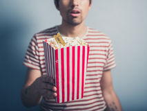 Young man with popcorn and cinema ticket Royalty Free Stock Image