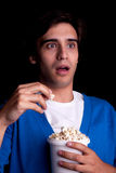 Young man, with popcorn watching Royalty Free Stock Image
