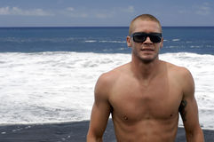 Young man portrait. Young caucasian male with sunglasses near ocean Royalty Free Stock Images