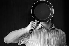 Young man portrait behind black frying pan Royalty Free Stock Photo