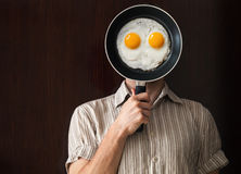 Young man portrait behind black pan with eggs Stock Photos
