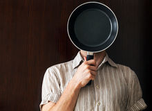 Young man portrait behind frying pan Royalty Free Stock Image