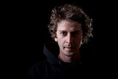 Young man portrait. Young curly hair caucasian man wearing black hooded sweatshirt. Low key portrait taken on black background Royalty Free Stock Photo
