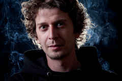 Young man portrait. Young curly hair caucasian man wearing black hooded sweatshirt. Low key portrait taken on black background full of smoke Stock Photo