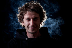 Young man portrait. Young curly hair caucasian man wearing black hooded sweatshirt. Low key portrait taken on black background full of smoke Stock Image