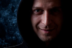 Young man portrait. Young curly hair caucasian man wearing black hooded sweatshirt. Low key portrait taken on black background full of smoke Stock Images