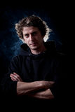 Young man portrait. Young curly hair caucasian man wearing black hooded sweatshirt. Low key portrait taken on black background full of smoke Royalty Free Stock Images