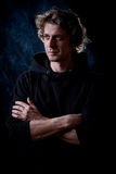 Young man portrait. Young curly hair caucasian man wearing black hooded sweatshirt. Low key portrait taken on black background full of smoke Royalty Free Stock Image