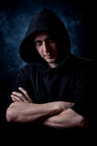 Young man portrait. Young curly hair caucasian man wearing black hooded sweatshirt. Low key portrait taken on black background full of smoke Royalty Free Stock Photos